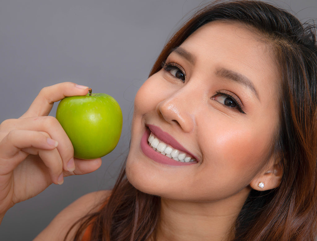 beautiful smile with green apple